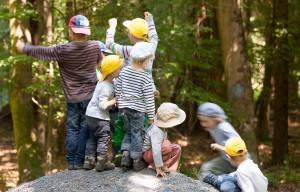 Kinder klettern auf einen großen Stein